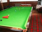A full sized billiard table and table football table in the games room