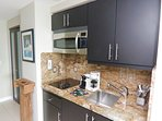 Kitchenette w/ custom cabinets and granite countertops.