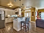 Kitchen with granite counters, gas stove, and stone back splash