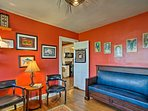 Warm red walls and eye-catching paintings turn the office into a comfortable space.