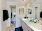 The en-suite master bathroom offers his-and-hers sinks and ample space.