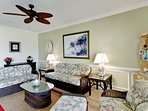 The living room features a rattan couch, love seat, and armchair.