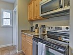 The fully equipped kitchen boasts new stainless steel appliances.