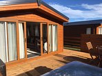 Decking area with sunken hot tub and easy access to lodge