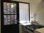 Cocina con estufa de gas y patio trasero para tender ropa