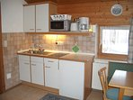 Kitchen with microwave, fridge with freezer compartment, and 2 ring hob.
