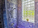 Enjoy a rinse in this walk-in shower lined with cerulean tiles!