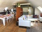 De ruime bovenverdieping met complete keuken en zithoek met schitterend zicht op de IJssel.