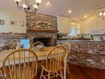 The dining table near the fireplace & kitchen seats 6 people.