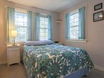 The upstairs guest bedroom features a full-size bed and windows that overlook some of the many trees surrounding the...