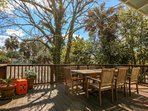 The porch features a tree-canopied teak dining table that comfortably seats 8 people.