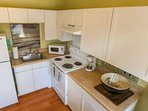 The kitchen is small but mighty with a stove, refrigerator, sink, microwave & coffee maker.