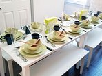 Dining table extends to accommodate dinner for 12 with plates, bowls, glasses, utensils galore