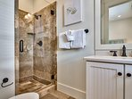 The ensuite to the second queen guest bedroom features the same style of elegantly-tiled walk-in shower as the other...