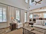 Crisp white walls and plush, cream sofas add coastal elegance to the home's main social area.