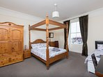 Large bedroom with view over harbour and four-poster bed