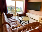 large sofa for family viewing on the 65' Smart TV and views to the beach and sea