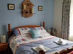 Kingsize bed in the main bedroom, with another lovely Devonshire Plaques shelving unit above.