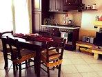 cucina con tv led, tavolo da pranzo e camino