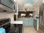 Marbled stone backsplash and full size stainless LE appliances