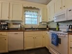 The kitchen features a dishwasher, stove, sink, coffee maker & mircrowave.