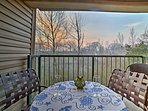 The covered deck includes patio furniture and wooded views.