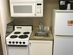 Microwave, range, oven, full size refrigerator  and sink.