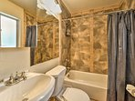 The full bathroom offers plenty of storage space and a shower/tub combo.