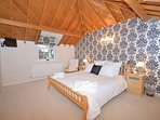 Super-king-size bedroom with TV and vaulted ceiling