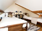 Twin beds in a pitched roof galleried bedroom