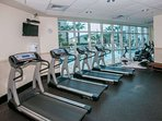 Fitness center with cardio equipment overlooking pool area