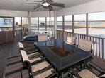 Large screened porch with plenty of dining/lounging space and a ceiling fan