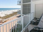 Private tiled balcony with lounge chairs overlooking the beach and Gulf