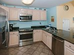 Fully equipped kitchen with granite counters and tile floors