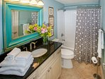 Queen ensuite bath with single vanity, tile floors and tub/shower