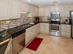 Fully equipped kitchen with stainless steel appliances and tile backsplash