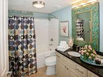 Master bath with single vanity, tiled floor and tub/shower