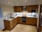 The newly fitted kitchen is large and well-stocked with oven, ceramic hob, microwave, dishwasher etc