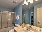 Sliding glass doors enhance the shower/combo in this en-suite bathroom.