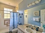 The beach-themed second bathroom includes a walk-in shower.