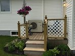 Back deck and another cottage entrance. Bike rack to left of deck.