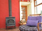 Relax in front of the wood burner in the sun room