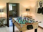 La sala giochi che ha anche una TV a schermo piatto, stufa a legna, e un divano a forma di L