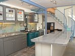Stylish kitchen with stair case leading up to the mezzanine floor