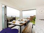 Upstairs open-plan dining area with bi-folding doors and beautiful sea views