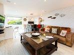 Open plan living space with bi-folding doors onto balcony