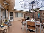 Upstairs patio shared with two other units includes a grill and outdoor dining space.