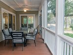 Step from the sun room or main room into the screened porch to dine around the table.