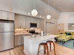 The fully equipped kitchen boasts sleek white surfaces, stainless steel appliances and stylish light fixtures.