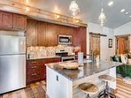 The kitchen features stainless steel appliances and a sizable island.